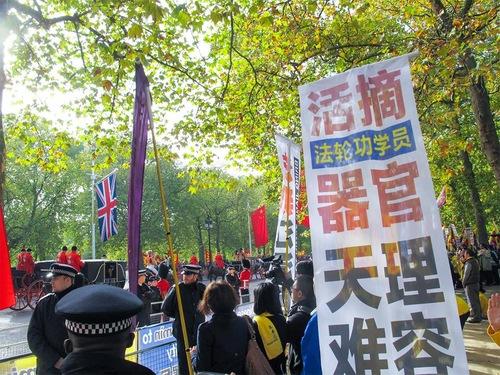 """Свитата на президент Ши преминава край банерите на Фалун Гонг, като този в близък план гласи: """"Небето забранява отнемането на органи от практикуващи Фалун Гонг""""."""