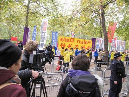 Медии заснемат протеста на практикуващи Фалун Гонг, които правят упражнения.